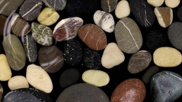 vídeos y material grabado en eventos de stock de gota de agua cayendo una rayas en las piedras bajo el agua. vista superior. - posición descriptiva