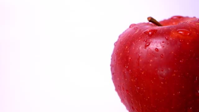 wassertropfen spritzen auf frischen roten äpfeln auf weißem hintergrund. natürliche frische bio gesunde früchte konzept, zeitlupe szene - apple stock-videos und b-roll-filmmaterial
