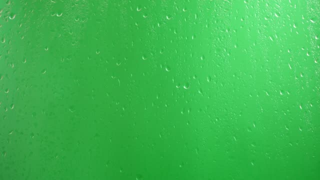 Water drops flow down the glass on a green background.