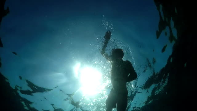 UNDERWATER: Water drops spraying on sea surface while active man swimming crawl video