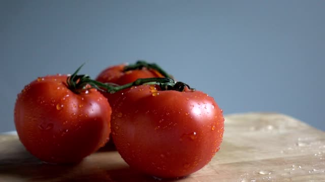 Water fall on tomato in slow motion raw video