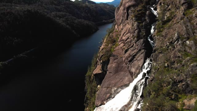 Water falling down the waterfall - Fjord landscape - Aerial drone footage