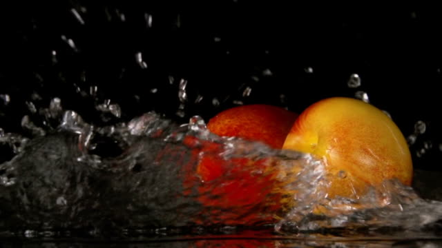 SLOW: A water flow falls on a nectarines on a black background video