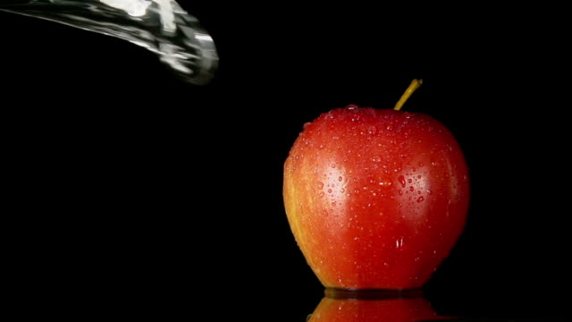 SLOW: A water flow falls on a red apple on a black background video