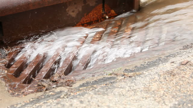 stockvideo's en b-roll-footage met water flowing down a storm drain - riool