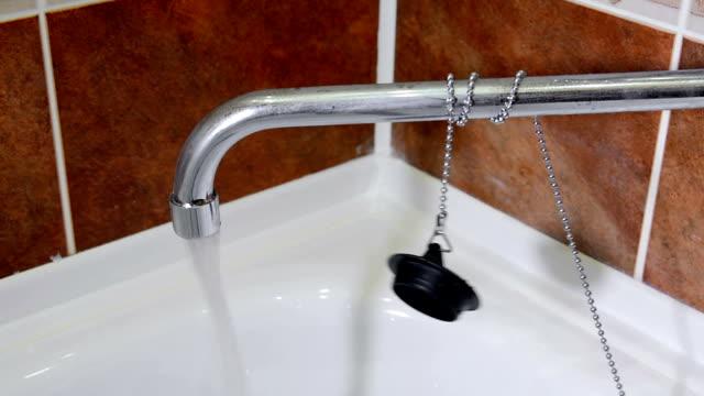 water flowing from the crane and stopper for a bathtub - kapsejsa bildbanksvideor och videomaterial från bakom kulisserna