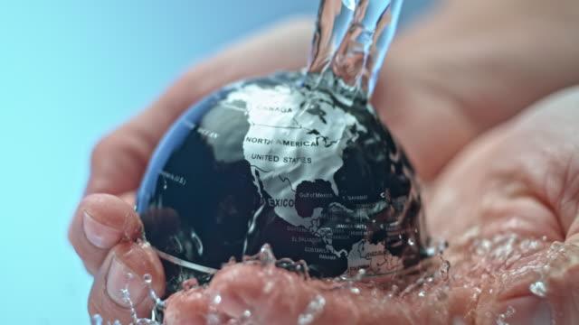 slo mo wasser fließt über eine kleine kugel in die person die hände statt - wassersparen stock-videos und b-roll-filmmaterial