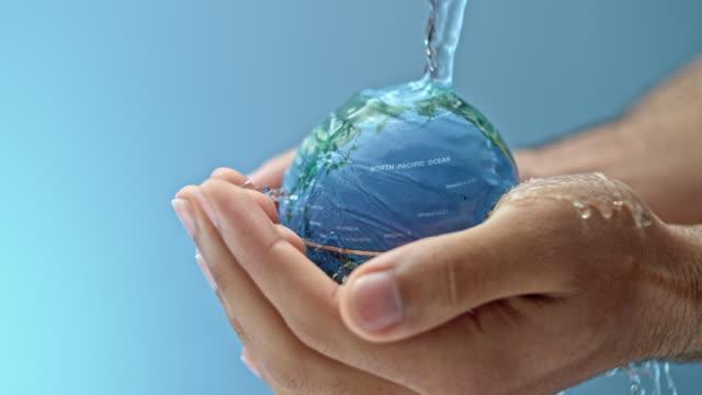 slo-mo-wasser fließt auf eine kleine weltkugel, die von einer person gehalten wird - wassersparen stock-videos und b-roll-filmmaterial