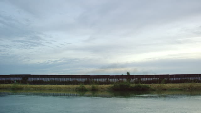 wasser fließt an einem leicht bewölkten tag bei sonnenuntergang parallel zur stahl-slat-grenzmauer (auf der us-seite) zwischen mexiko und den vereinigten staaten - schilf stock-videos und b-roll-filmmaterial