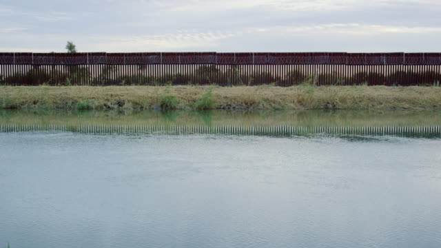 Water Flows Down a Canal Running Parallel to the Steel-Slat Border Wall (on the US Side) between Mexico and the United States on a Partly Cloudy Day at Sunset