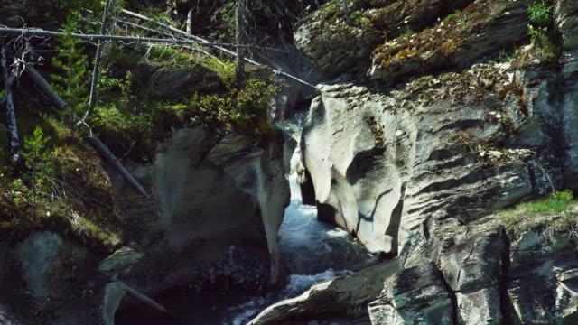 Water Flows Down Rock Faces of a Waterfall and Joins a Blue-Green-Colored Stream in a Canadian Mountain Environment on a Sunny Day