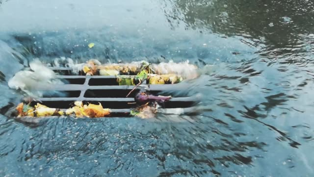 Water from the road drains into the storm drain sewer collector with grate during the rain. Main channel of the drainage network. Rainy weather in city. Bad and dangerous conditions for traffic