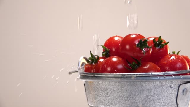 Water is poured on tiny tomatoes white background - vídeo