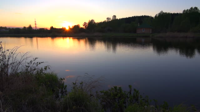 Water of the small lake slowly moving in sunset with small house on the shore
