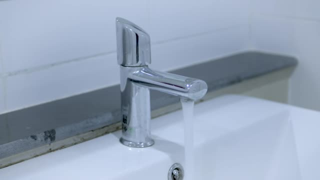 Water pouring from the chrome tap.