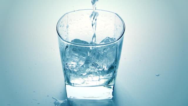 Wasser gießen in ein Glas mit Eiswürfeln – Video