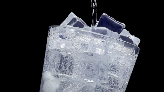 Pouring water into glass of ice at slow motion video