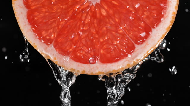 Water Pouring over the Backlit Juicy Grapefruit Slice