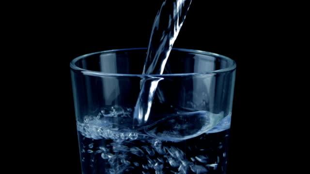 water pours into  glass on black - tap water filmów i materiałów b-roll