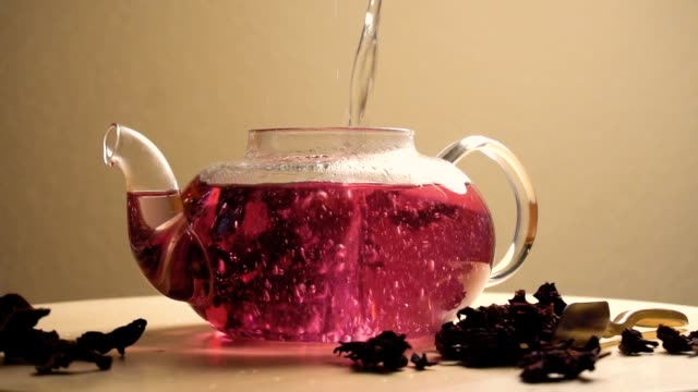 water puring in teapot with red karkade tea - teapot stock videos & royalty-free footage