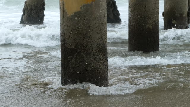 Water receding from under a pier slow motion
