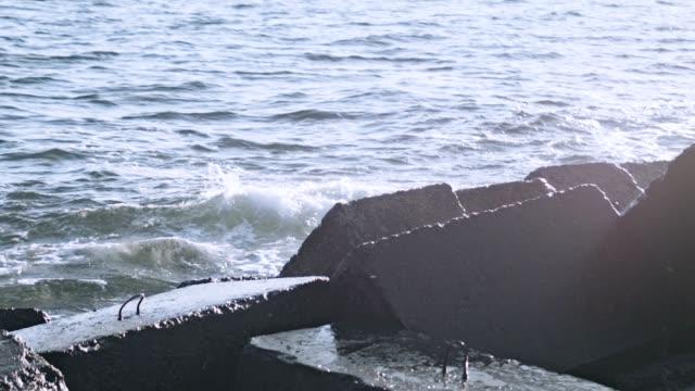 Water rocks. Rocks in water. Breakwaters on ocean shore. Crashing waves video