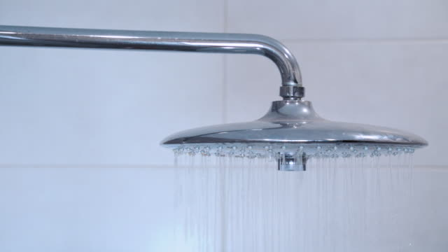 Water running from shower head and faucet in modern bathroom. Rain Shower turned, ceiling shower head closeup in the shower stall.