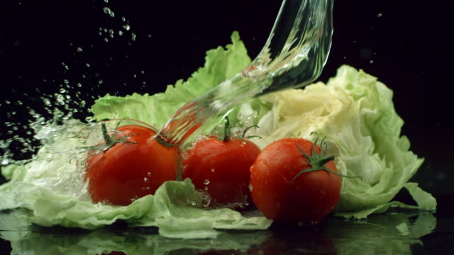 Water splashing onto lettuce and tomatoes, slow motion video