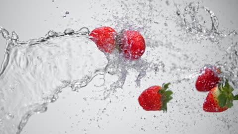 vidéos et rushes de slo, dans le missouri, eau et des fraises éclaboussures dans l'air - fraise