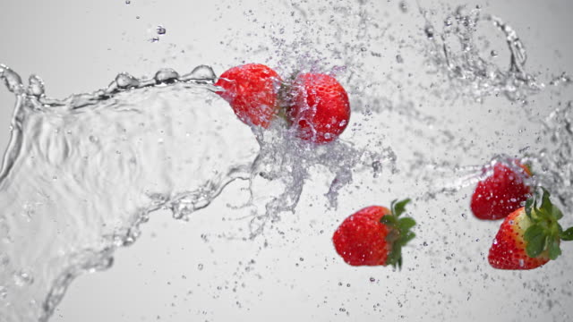 SLO MO Water splashing strawberries in the air video