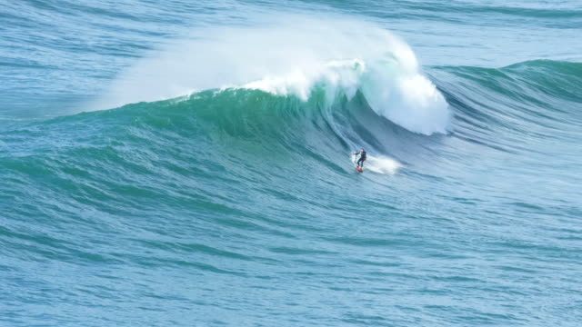 water sport enthusiast surfs in ocean sailing away from wave