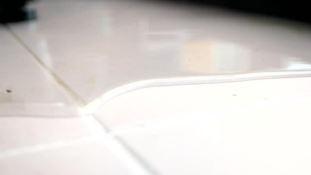 water spreads across floor white tile reflecting window