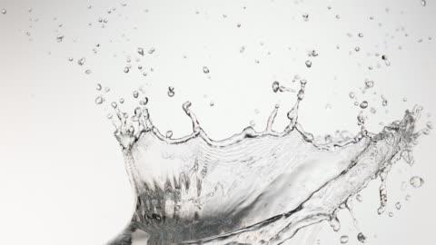 wasser spurting aus weißen hintergrund, slow-motion 4k - wasser stock-videos und b-roll-filmmaterial