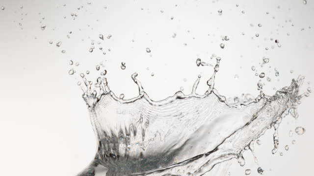 vídeos de stock e filmes b-roll de water spurting out against white background, slow motion 4k - water splash