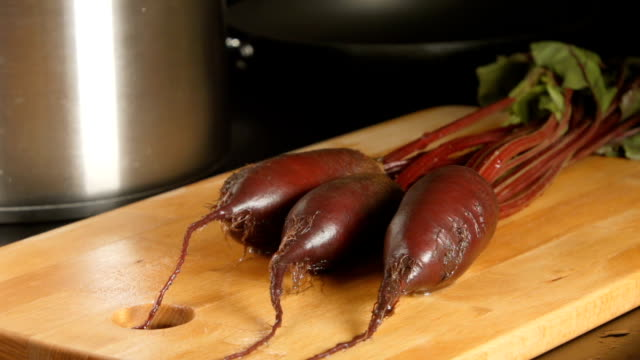 SLOW MOTION: Water stream falls on a beets on a cutting board in a kitchen video