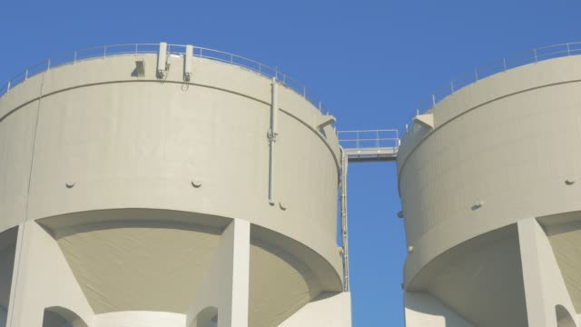 Water tanks made of concrete against blue sky 4K 2160p UHD slow panning video - Water tower in front of blue sky 4K 3840X2160 panning UHD footage