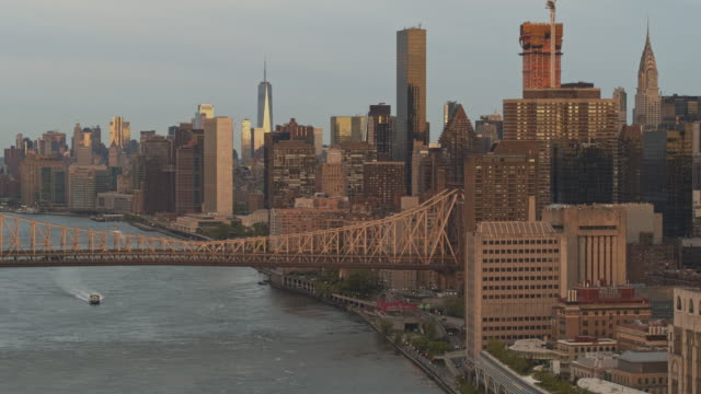 A water taxi passing under Ed Koch Queensboro Bridge. Aerial drone footage with the cinematic panning and descending camera motion.