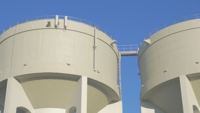 Water tower details against blue sky 4K 2160p UHD slow panning video - Water tanks in front of blue sky 4K 3840X2160 UHD footage