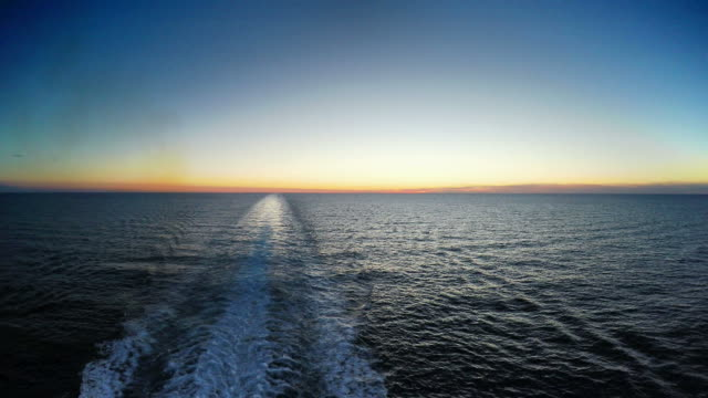 Water trace behind boat in sunset video