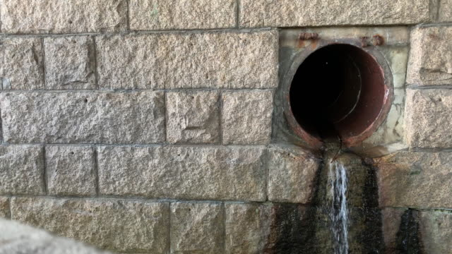 Water Trickles from a Drain Pipe in the Side of a Stone Wall