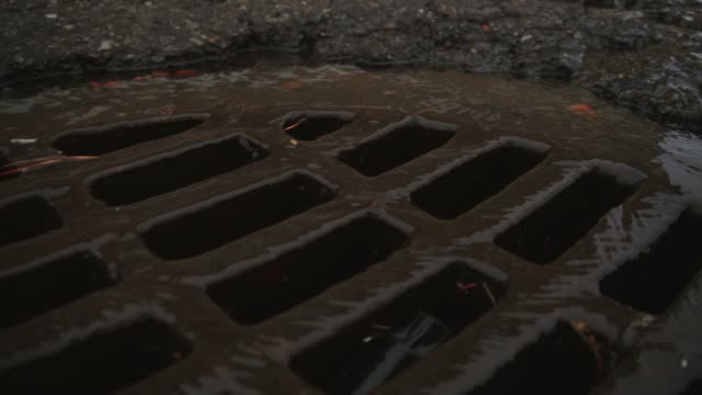 Water Trickles into a Round Grated Sewer Drain