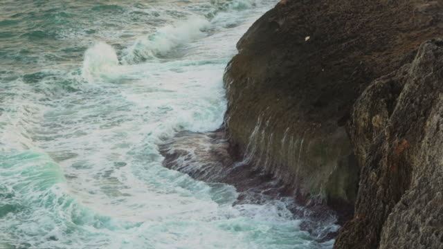 vídeos de stock e filmes b-roll de water waves crashing on rocky shore, white foam forming sea surface - ambiente vegetal