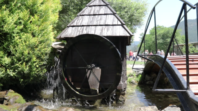 Water Wheel Beside Bridge In Nature On Sunny Day