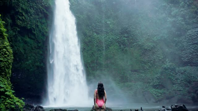 waterfall and woman traveler in bali, indonesia. tropical forest and waterfall - bali filmów i materiałów b-roll