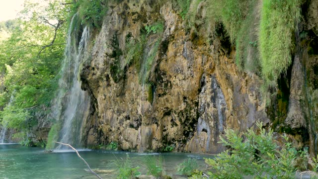 Waterfall flowing into the clear blue lakes of the Plitvice National Park in Cro video