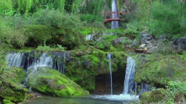 Waterfall in lake pond water and green trees. Wood foot arch bridge. Spirit-nurturing peaceful Zen aspect.
