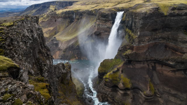 Waterfall plunging from a high plateau into massive canyon
