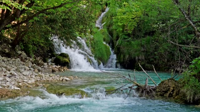 Waterfall with turquoise water in the Plitvice Lakes National Park, Croatia.