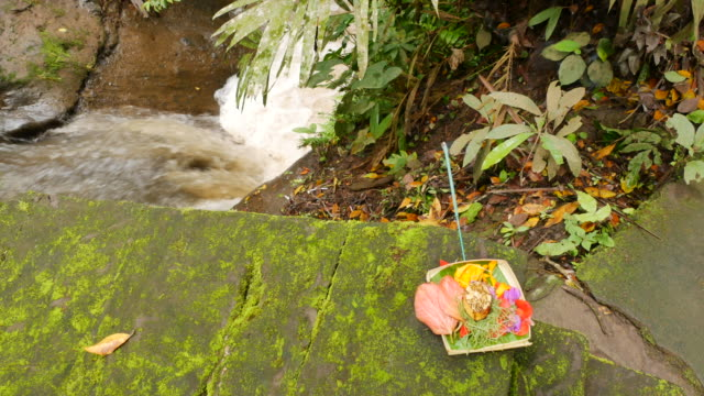 Waterflow and canang sari offering in a balinese temple