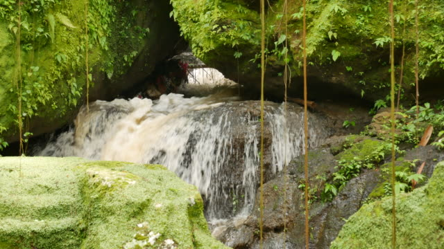 Waterflow in the temple surrounded by rocks covered with bright green moss